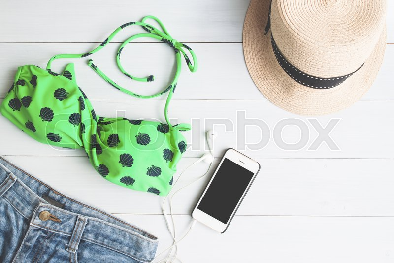 Overhead view of bikini and short jeans, girl accessories with smartphone on white wooden background, Summer travel concept, stock photo