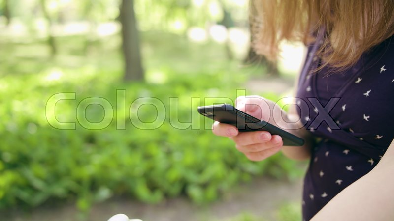 Woman with pram while taking a walk in the park using a cellphone. Dolly shot. Soft focus, stock photo