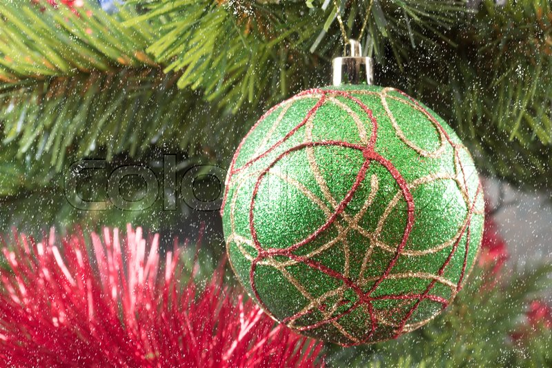 A green Christmas tree ball on a branch against the background of branches and a red garland, stock photo
