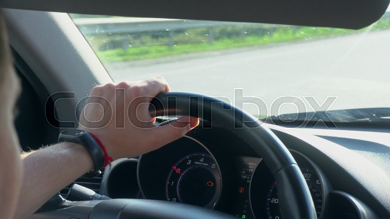 Inside a car. A man\'s hands on the steering wheel. Close-up shot, stock photo