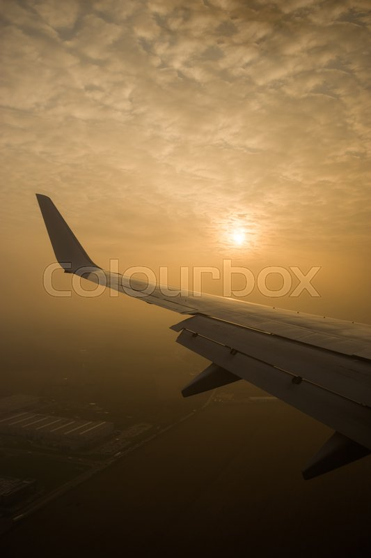 The sun is through the clouds. View from the airplane window, stock photo