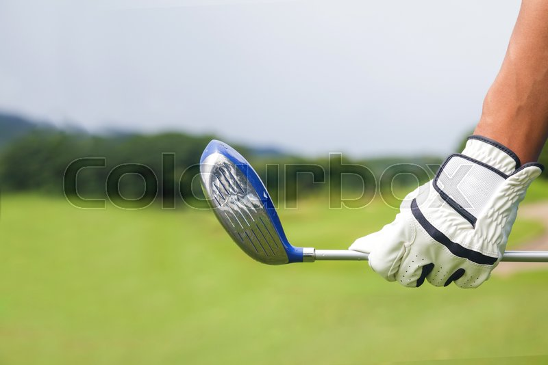 Golf player holding a golf club on golf course, stock photo