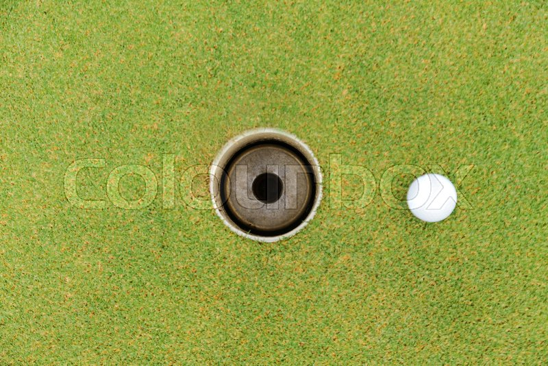 Golf hole and golf ball on green grass on golf course, stock photo