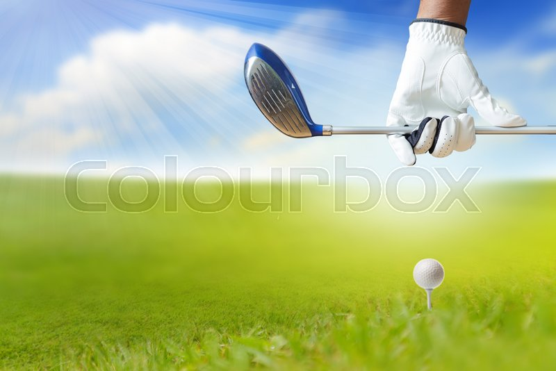Close up of Golf player holding a golf club on golf course under blue sky, stock photo