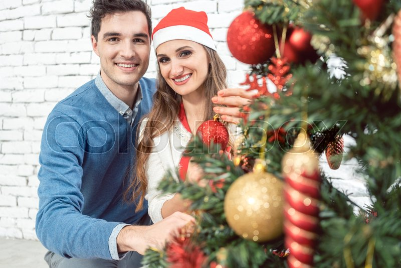 Couple at home decorating tree for Christmas with ornaments, stock photo