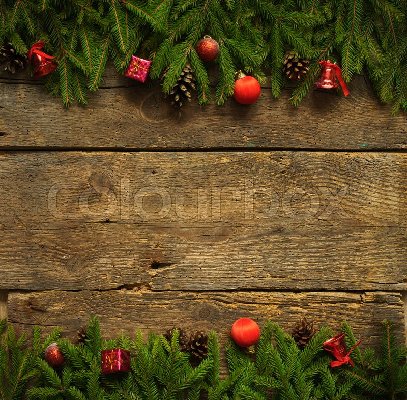 Christmas border with fir tree branches, cones and christmas decorations on rustic wooden boards ready for your design, stock photo