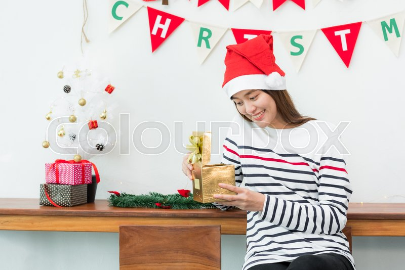 Asia woman smile when open gold xmas gift box at holiday party with decoration flag at background,giving Christmas party present,wow feeling and happiness moment, stock photo