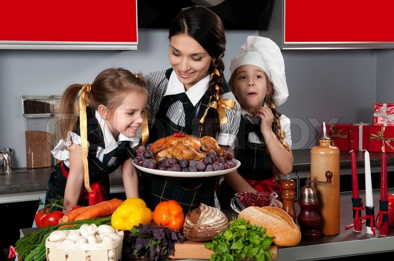 Image of 'mother with two daughters in the kitchen preparing Christmas dinner with turkey and vegetables'