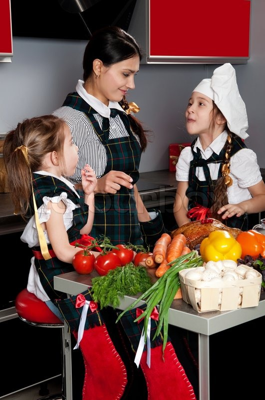 Mother with two daughters in the kitchen preparing Christmas ...
