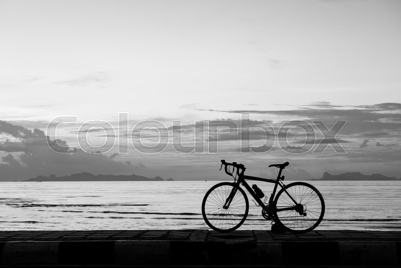 Silhouette bicycle on the beach sunset background,black and white tone, stock photo