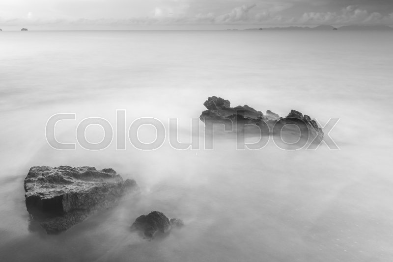Black and white mystical photo - sea waves and cobblestones on the beach close up, stock photo