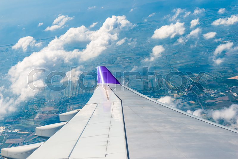 Wing of the aircraft view from the window, the fields and the city of Thailand below, stock photo