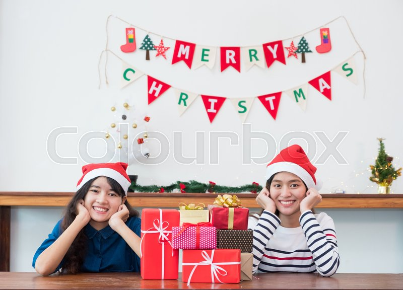 Asia girl friends wear santa hat in Christmas and new year party with group of red gift box with smiling face,Xmas gift giving,Lovely friendship, stock photo