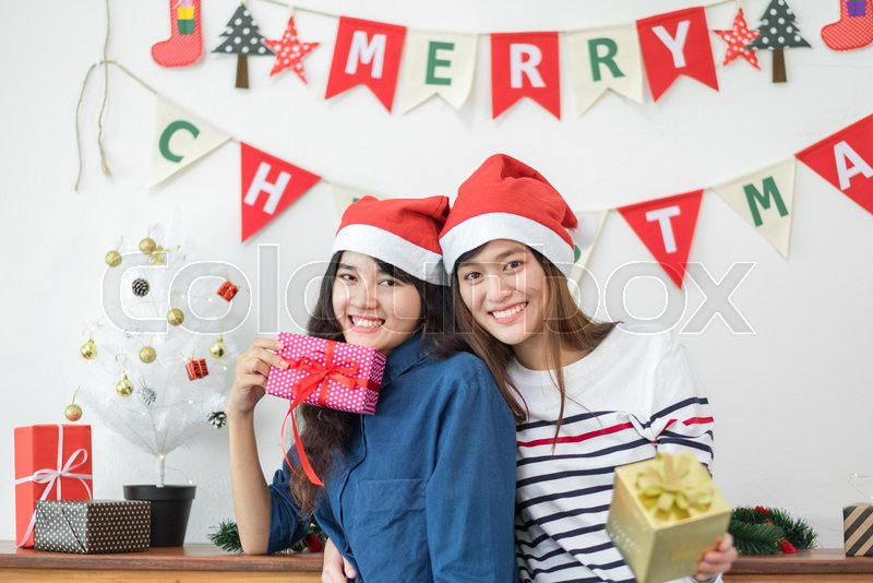 Asia girl friends wear santa hat in merry christmas and new year party exchange red gift box each other with smiling face,Xmas gift giving,Lovely lesbian couple lifestyle, stock photo