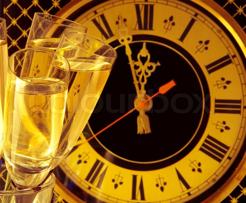 Christmas card Glasses of champagne on New Year\'s Eve against an ancient wall clock, stock photo