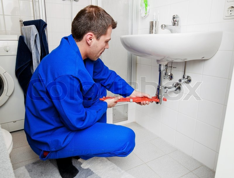 A Plumber Repairing A Broken Sink In Stock Photo