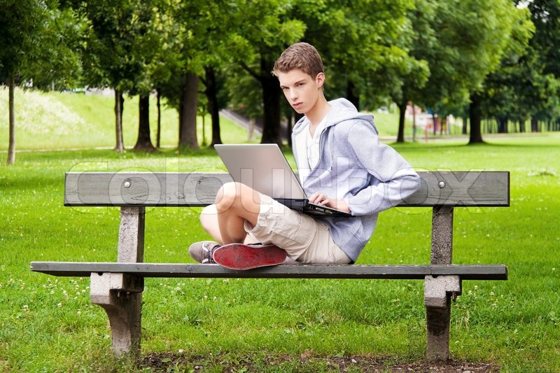 A Teenager With Laptop Outdoors Sitting In The Park Mobile