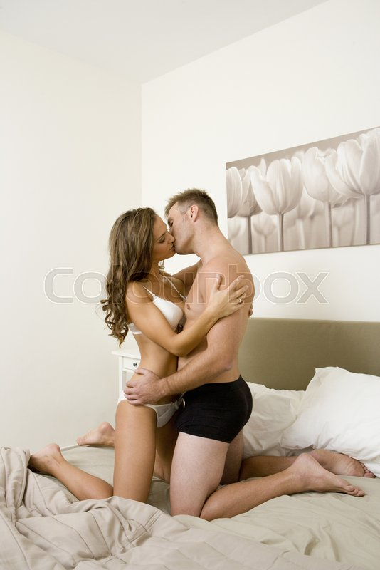 German young wife kissing in bed