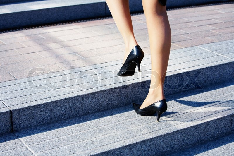 Stock image of 'Businesswoman taking step to higher level on stairway'