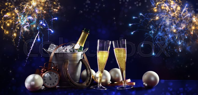 new year background banner with champagne bottle and glasses christmas decorations and fireworks against a dark blue background in panoramic format stock