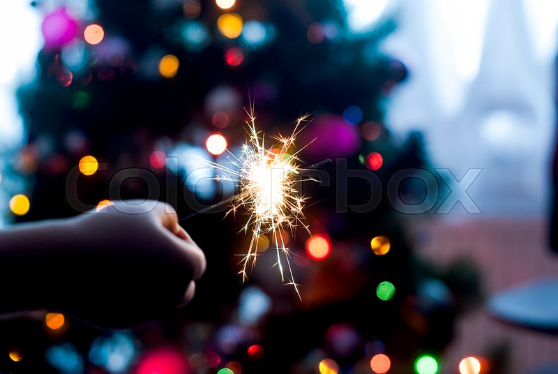Burning Bengal Lights On Christmas Tree Light Background Against Defocused Close Up