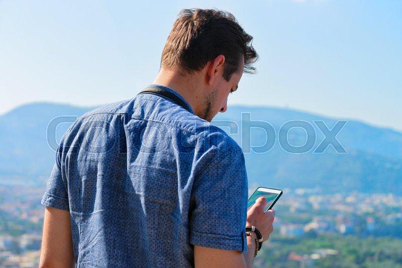 Man looking at mobile phone in Marina Grande in Sorrento, Tyrrhenian sea, Amalfi coast, Italy, stock photo