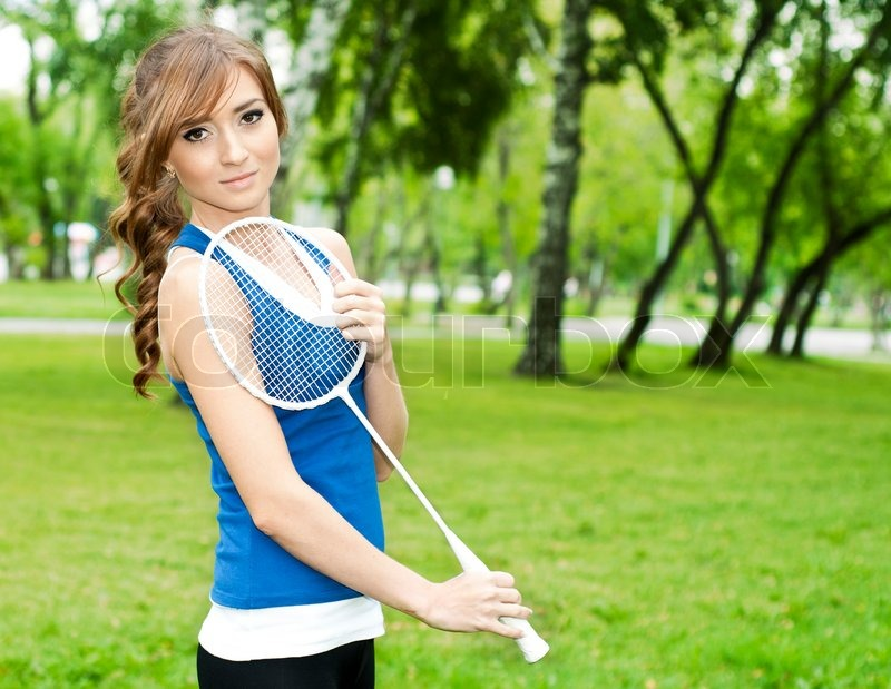 Beautiful Young Woman With Badminton Racket  In The Summer