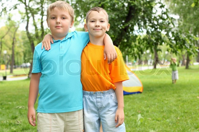 two boys standing next to each other in the summer park stock