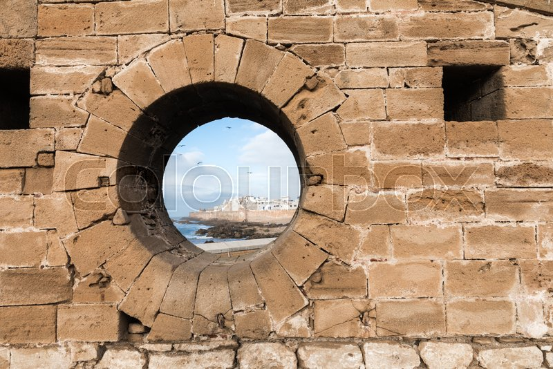 Classic view of medina Essaouira through a hole in the wall of the fortress, Morocco. UNESCO world heritage site, stock photo