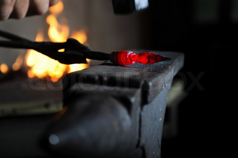 Blacksmith forges a red-hot iron in the ... | Stock Photo ...