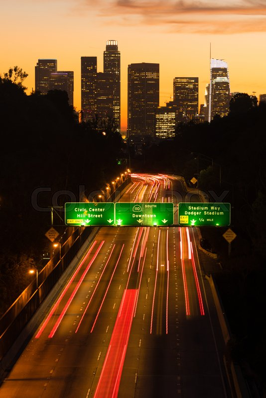 Light streaks from brake lamps flow across the foreground ad sunset falls on Los Angeles, stock photo