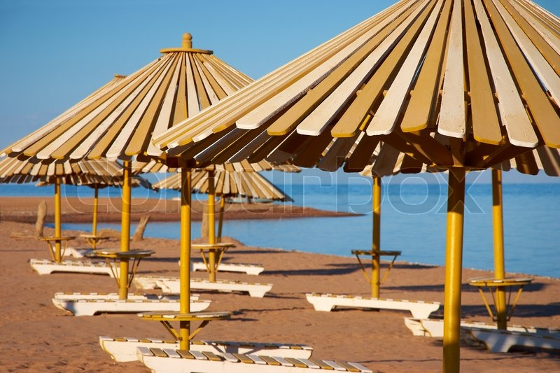 View Of Wooden Umbrella And Chairs On The Beach Stock