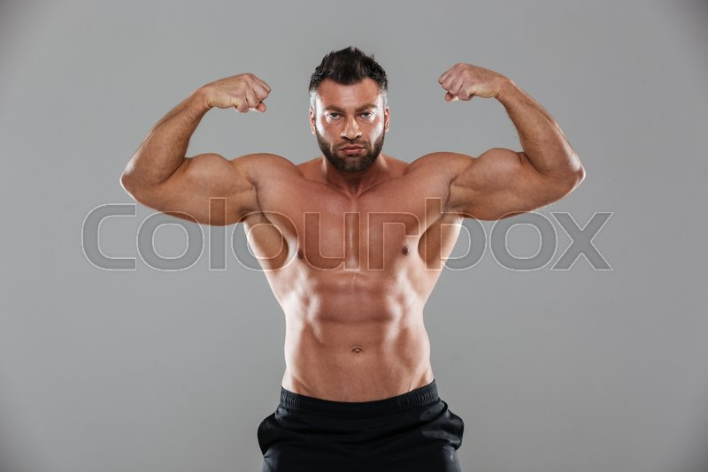 Portrait of a muscular strong shirtless male bodybuilder flexing ...