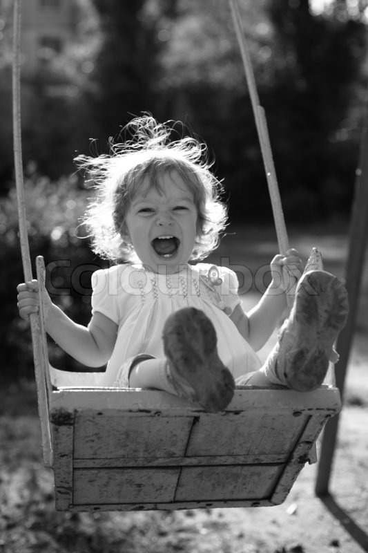 Playing on the swings black and white photo with orange filter effect shallow depth of field back lighting stock photo colourbox