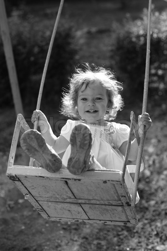 Child playing on the swings black and white photo with yellow filter effect shallow depth of field back lighting stock photo colourbox