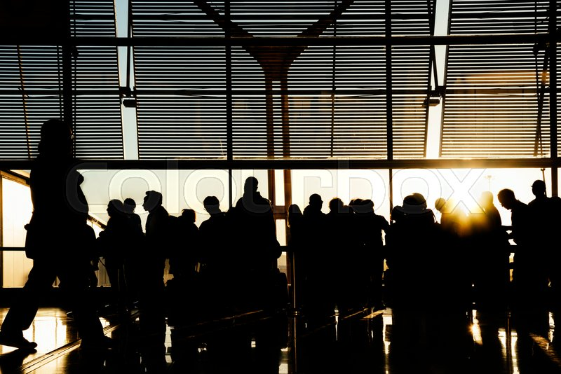Silhouettes of business people traveling on airport; waiting at the plane boarding gates, stock photo
