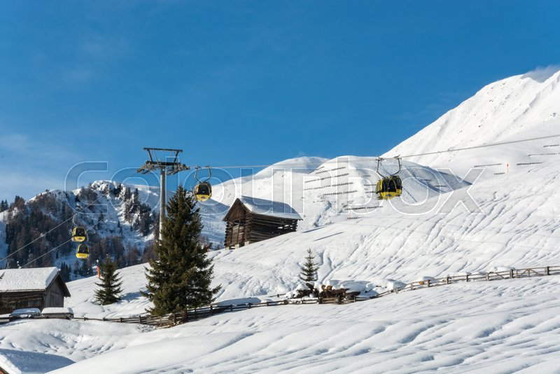 Stock Bild von 'Yellow gondolas in ski resort Serfaus Fiss Ladis in Austria with snowy mountains and blue sky'
