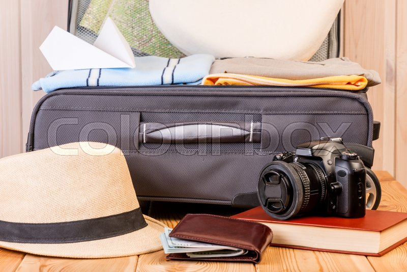 Gray male suitcase and accessories for a long journey close-up on a wooden table, stock photo