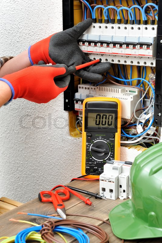 Stock image of 'Young electrician technician fixes the electric cable to the magnetothermic switch with the screwdriver'