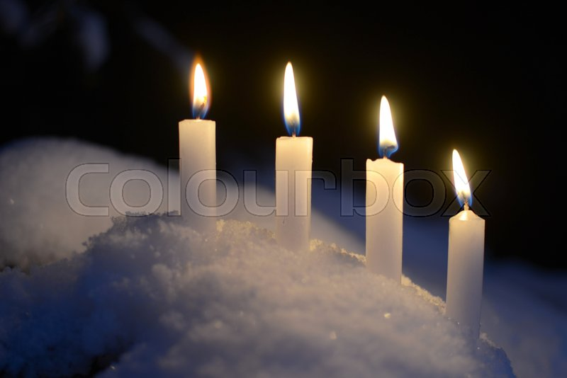 Stock Bild von 'Four white candles in snow.'