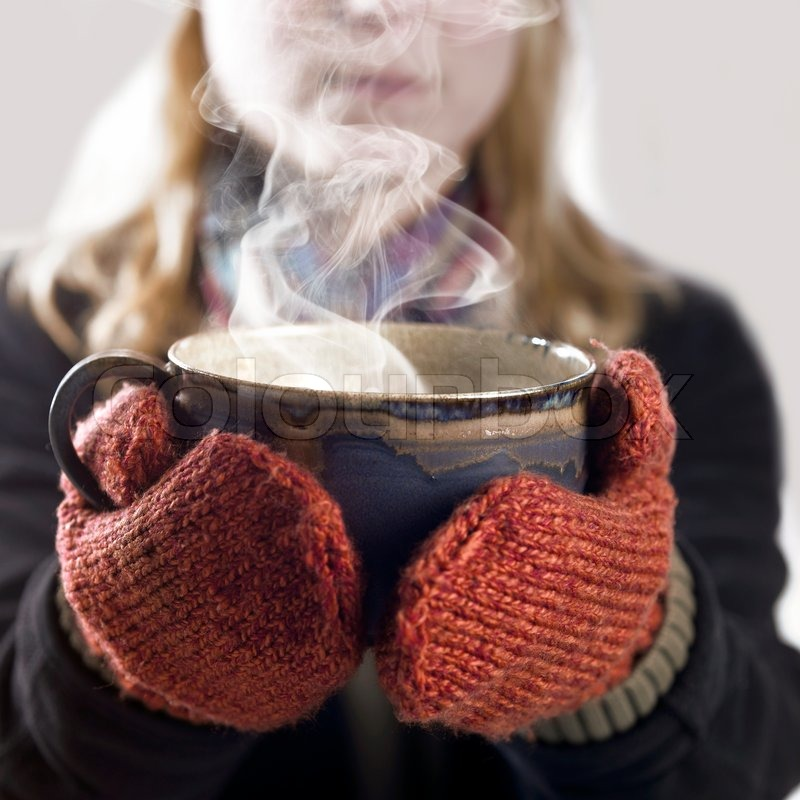 Detail of a woman with woolen gloves holding a hot steaming cup, stock photo
