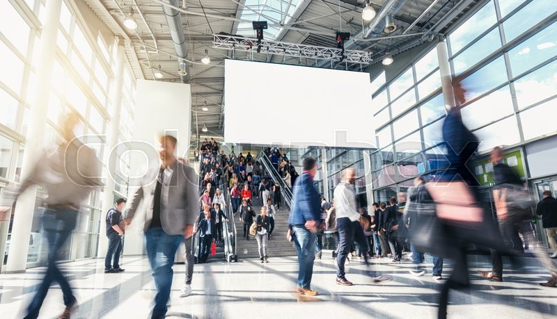 Stock Bild von 'business people walking at a tradeshow entrance including banner for copy space . ideal for websites and magazines layouts'