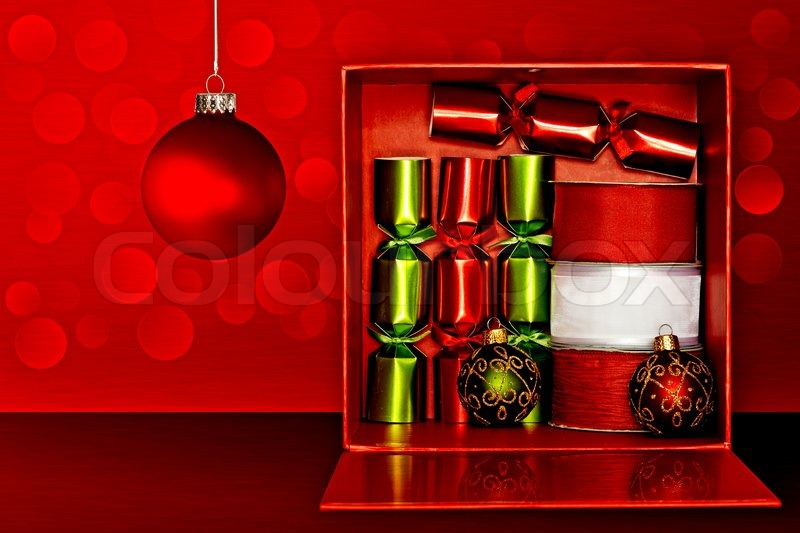Red Gift Box Filled With Red & Green Party Favors, Decorative Red & White Ribbon And Red, Green & Gold Glitter Christmas Ornaments Over Red Textured Background With LED Lights, stock photo