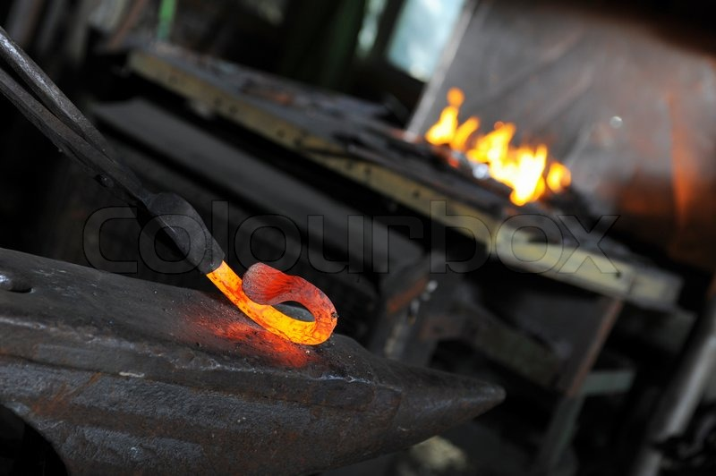 Blacksmith Forges A Red Hot Iron In The Forge Stock