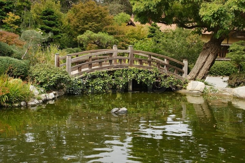 A Small Pond And A Decorative Wooden Bridge In The