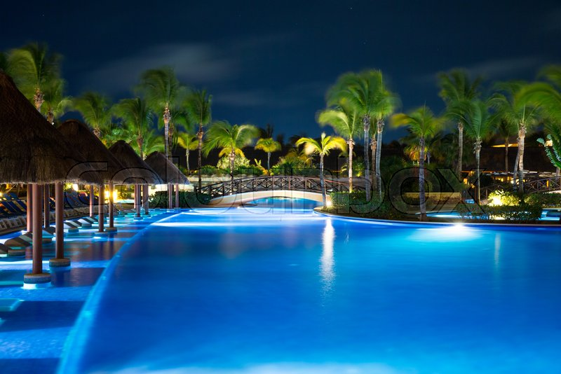 Swimming pool in night illumination. tropical resort at night, stock photo