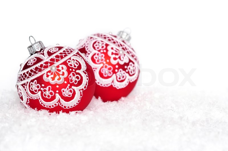 Red Christmas Balls With Pattern On Snow Over White Background