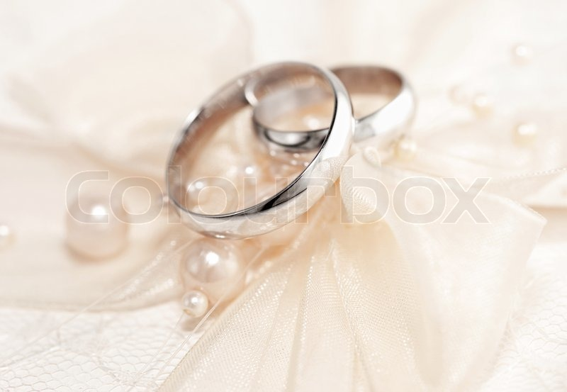 Pair Of Golden Wedding Rings Over Invitation Card
