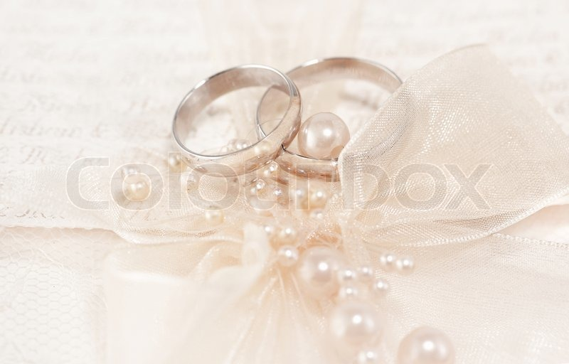 pair of golden wedding rings over invitation card decorated with, Wedding invitations