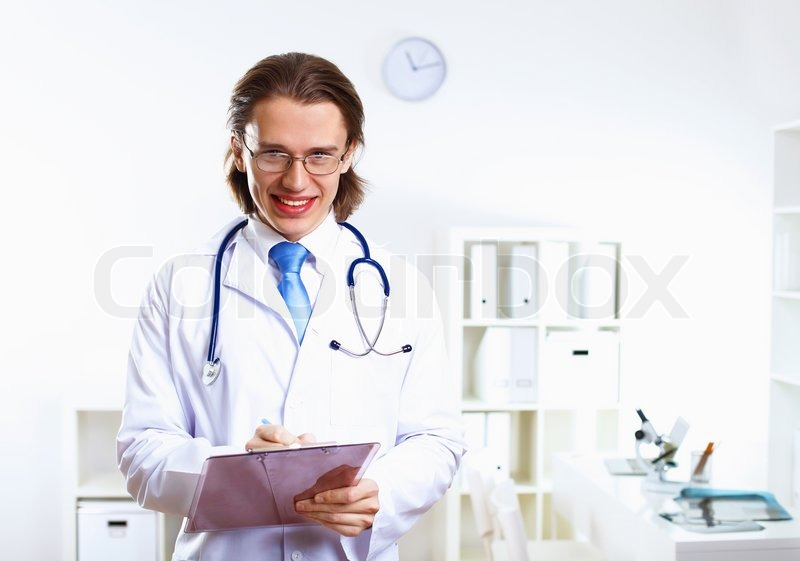 Young confident and friendly doctor in medical office, stock photo